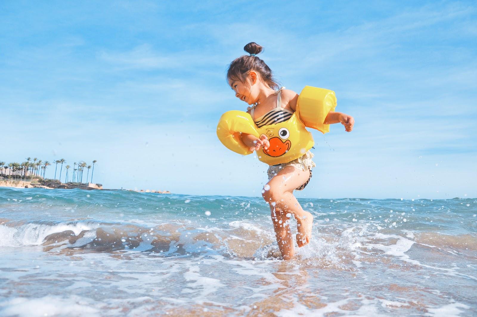 Kind in de zee met zwembandjes - Musthaves voor een kampeervakantie